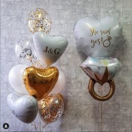 Композиция на помолвку из шаров конфетти и белых сердец с кольцом и надписью: She said yes